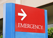 An exterior directional sign for a hospital emergency department.