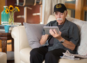 A Veteran sitting on a couch and using a handheld tablet to participate in a telehealth session.