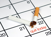 A cigarette ripped in half on top of a calendar with the words 'Quit today'