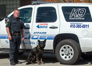 Sgt. Hartman and his police dog 'Honz' standing next to a police vehicle.