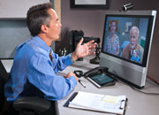 A physician consults with a veteran remotely from his office via telehealth equipment during a clinic visit.