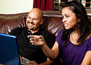 A couple sitting on a couch and looking at a computer laptop screen.