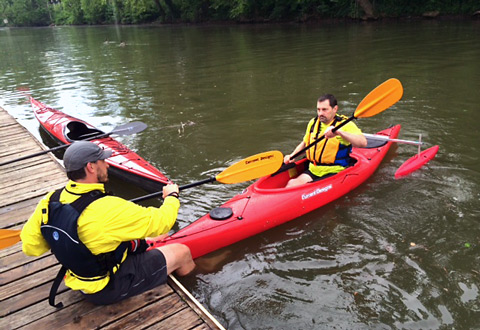 A Veteran sitting in a kayak on the river receives instructions on how to paddle.