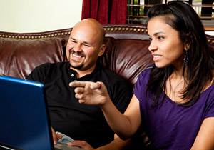 Smiling couple sitting on a couch and using a laptop computer.