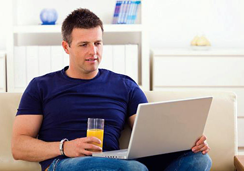 While sitting in his living room and drinking a glass of orange juice, a young male Veteran reviews the MyHealtheVet website on a laptop.