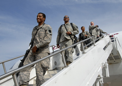 A group of returning servicemembers getting off a plane.