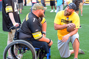 A veteran in a wheelchair talks with a player from the Pittsburgh Steelers on the turf at Heinz Field.