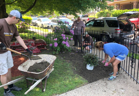 VA and UPS employees planting flowers and spreading mulch.