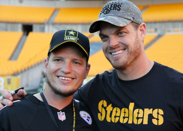 A Veteran poses for a photo with a Steelers player.