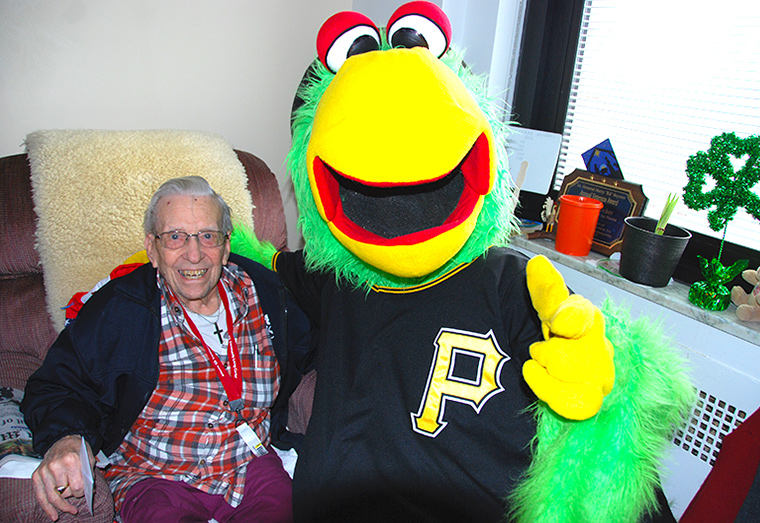 A Veteran poses for a photo with the Pittsburgh Pirates Parrot mascot.